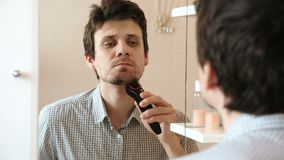Волосы на лице бритья машины Брить молодого красивого человека сухой с электрическим триммером видеоматериал