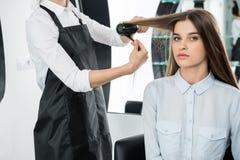 Волосы парикмахера чистя щеткой женщины стоковые изображения rf