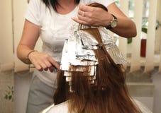 Волосы расцветки парикмахера в студии стоковые фото