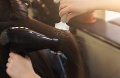 Волосы ` s женщины засыхания парикмахера в салоне красоты Стоковая Фотография