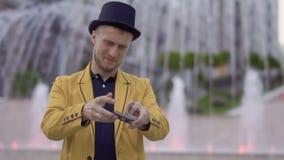 Волшебник в шляпе и желтой куртке умело двигая играя карточки в руках видеоматериал