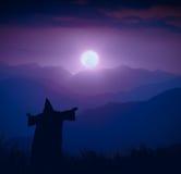 Волшебник стоя на холме и радушном поднимать луны Стоковые Изображения RF