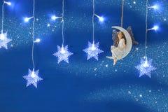 Волшебное изображение рождества маленькой белой феи с ярким блеском подгоняет сидеть на луне над голубым gar предпосылки и снежин Стоковые Фотографии RF