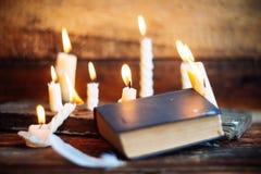 3 волшебных книги в свете горящей свечи на деревянном столе в темноте Стоковое Изображение