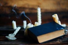 3 волшебных книги в свете горящей свечи на деревянном столе в темноте Стоковая Фотография RF