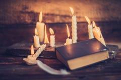 3 волшебных книги в свете горящей свечи на деревянном столе в темноте Стоковые Фото