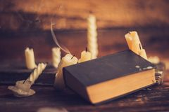3 волшебных книги в свете горящей свечи на деревянном столе в темноте Стоковая Фотография