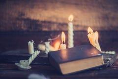 3 волшебных книги в свете горящей свечи на деревянном столе в темноте Стоковые Изображения RF