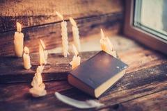 3 волшебных книги в свете горящей свечи на деревянном столе в темноте Стоковое Изображение RF
