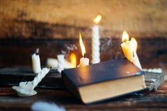 3 волшебных книги в свете горящей свечи на деревянном столе в темноте Стоковые Изображения
