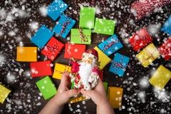 Волшебство рождества, 2 руки детей держит Санта Клауса с надеждой с Стоковые Изображения