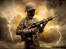 Вооруженное положение солдата в неясной погоде стоковое фото rf