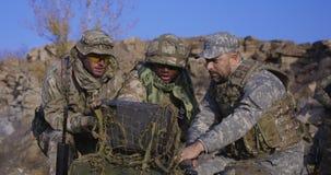 Вооруженный Афро-американский солдат смотря компьютер стоковое фото rf
