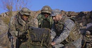 Вооруженный Афро-американский солдат смотря компьютер стоковые изображения