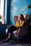 Воодушевленная девушка сидя в кресле перед окном и Стоковая Фотография