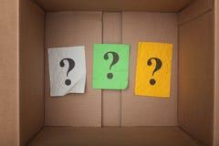 Вопросительные знаки внутри картонной коробки Стоковое Фото