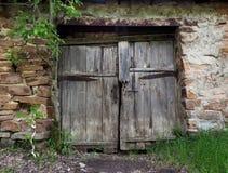 Ворота получившегося отказ старого полу-загубленного каменного дома между лесом стоковое фото rf