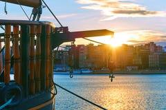 Ворот с крюками на кормке деревянного корабля в порте вечера с городским пейзажем на предпосылке Стоковая Фотография RF