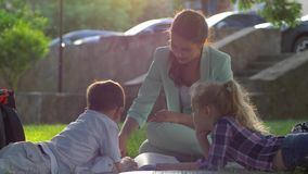 Воспитательные уроки, учитель дамы прочитали книгу для мальчика и девушки сидя на зеленой траве в природе в солнечном свете сток-видео