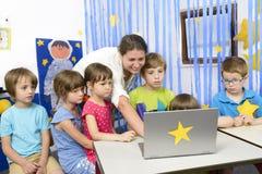 Воспитатель окруженный детьми на детском саде Стоковое Изображение