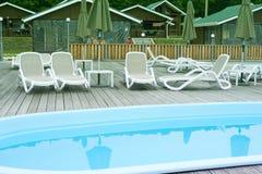 Воссоздание воссоздания загородного клуба ослабляет зонтик lounger солнца лесных деревьев дома бассейна деревянный стоковая фотография rf
