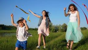 Воссоздание детей, симпатичная сестра с остатками наслаждения маленького брата под открытым небом вдоль реки сток-видео