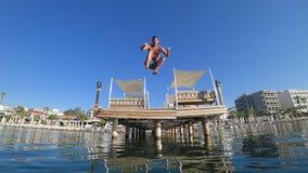 Воссоздание лета, счастливый мужчина скача от пристани к морю и давая большой палец руки вверх под водой и воздушными пузырями акции видеоматериалы