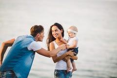 Воссоздание семьи на открытом воздухе с видами на море молодая кавказская семья с годовалым ребенком в оружиях, стильных одеждах  стоковые фото
