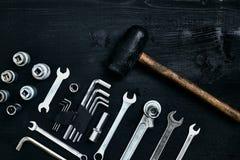 Восстанавливать автомобиль Комплект ремонта оборудует ключи наговора, молоток и отвертку на черной деревянной предпосылке конец в Стоковое Фото