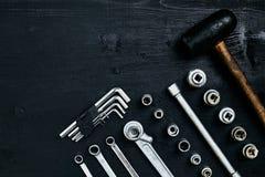 Восстанавливать автомобиль Комплект ремонта оборудует ключи наговора, молоток и отвертку на черной деревянной предпосылке конец в Стоковое Изображение