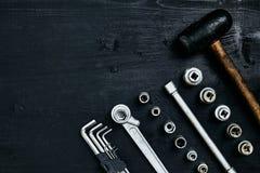 Восстанавливать автомобиль Комплект ремонта оборудует ключи наговора, молоток и отвертку на черной деревянной предпосылке конец в Стоковые Фото