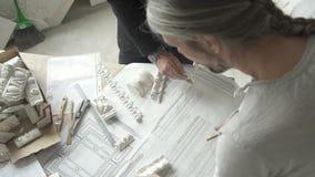 Восстановители мастеров работая с украшениями светокопии и гипсолита на таблице в светлой мастерской сток-видео