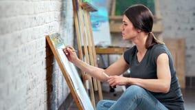 Восторженная молодая женщина создавая деятельность иллюстрации на взгляде со стороны художественной мастерской сток-видео