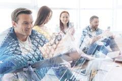 Восторженные коллеги используя мобильные телефоны в офисе Стоковое фото RF