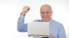 Восторженный бизнесмен использует ноутбук для сообщения и жестикулирует счастливый стоковые фото