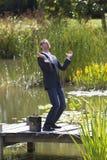 Восторженный бизнесмен хлопая для продвижения работы на мосте около воды Стоковое фото RF
