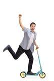 Восторженный молодой человек ехать самокат и показывать с его рукой Стоковые Изображения