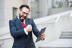 Восторженный предприниматель выражая ободрение пока используя цифровой планшет стоковые фото