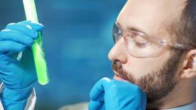 Восторженный профессиональный мужской химик смотря на процессе диффузии зеленое реактивного в beaker видеоматериал