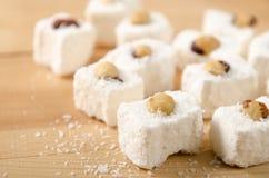 Восточные помадки, турецкое наслаждение с кокосом шелушатся, фундуки на деревянном столе стоковые фото