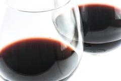 2 восхитительных прозрачных стекла с красным вином на белой предпосылке - близкое поднимающим вверх Стоковые Изображения