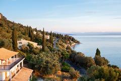 Восход солнца лета на побережье, острове Корфу, Греции Взгляд побережья, столица острова и албанские горы стоковая фотография