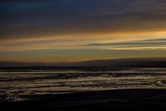 Восход солнца над заливом Бристоля от дока на Ekuk Аляске во время отлива стоковое фото rf