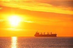 Восход солнца над морем с грузовим кораблем плавания перевозка Логистика shipping стоковая фотография rf