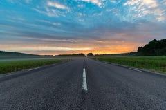Восход солнца над прямой дорогой через зеленые поля Стоковые Изображения RF