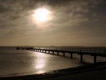 Восход солнца над холодом море Пристань протягивая в безграничность стоковые изображения