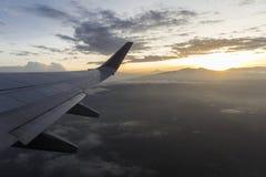 Восход солнца от самолета в полете с взглядом своего крыла и солнца позади Стоковое Изображение RF
