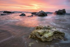 Восход солнца с живым небом апельсина и красного цвета, утесами на переднем плане Стоковое Изображение RF