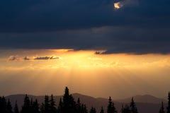 Восход солнца в горах Планы елевых верхних частей и лучей ` s солнца делают их путь через пики облаков Справочная информация Стоковая Фотография RF