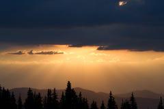 Восход солнца в горах Планы елевых верхних частей и лучей ` s солнца делают их путь через пики облаков Справочная информация Coni Стоковое Фото